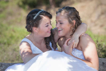 two brides smile and embrace in nature surroundings on sunny day Reklamní fotografie
