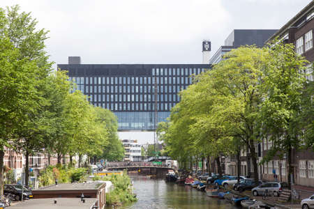 building of amsterdam university on roeterseiland seen over canal