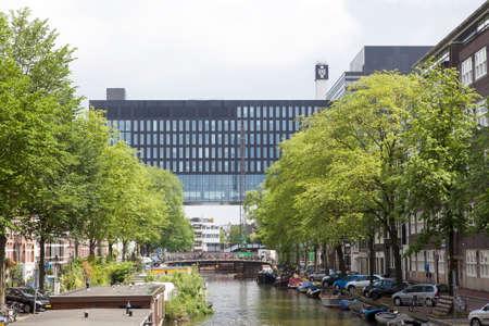 gebouw van de Universiteit van Amsterdam op het Roeterseiland gezien over kanaal