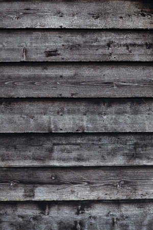 old barn: vertical part of old black and grey wooden barn wall
