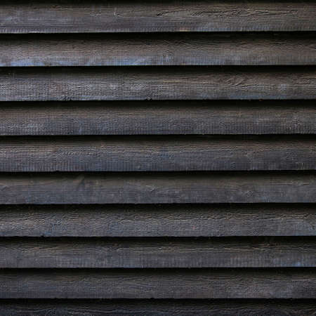 sombre: square part of black wooden fence or part of black painted barn Stock Photo