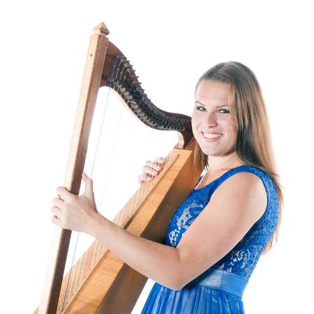 白い背景に、スタジオで小さなハープと笑顔の若い白人女性が立っています。