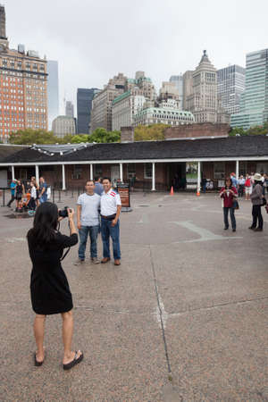 five month old: tourist takes pictures of people and downtown manhattan in castle clinton in battery park