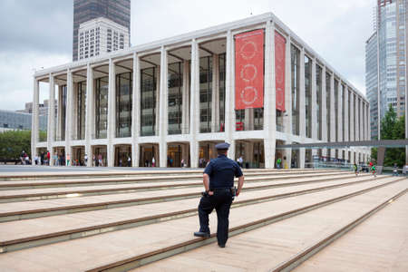 upper school: new york city, 12 september 2015: police officer stands on steps near philharmonic orchestra part of lincoln centre in new york city