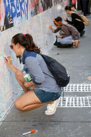 9 11: new york city, 11 september 2015: young women sit on pavement near ground zero in new york city and write texts on wall for patriot day
