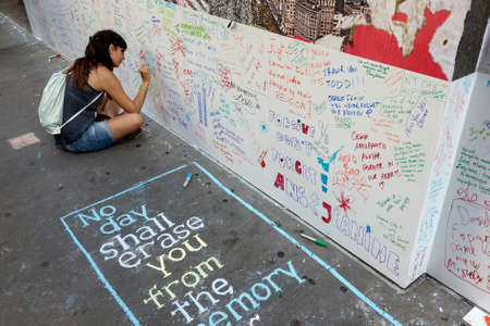 new york city, 11 september 2015: young woman sits on pavement near ground zero in new york city and writes on wall for patriot day