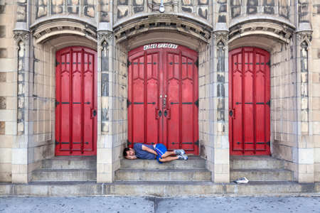 ave: new york city, usa, 15 september 2015: man sleeps in front of church door on 7th ave in new york city