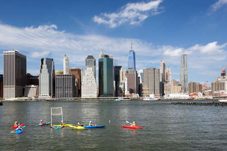 kayak polo in east river new york city with lower manhattan skyline in the background on sunny day