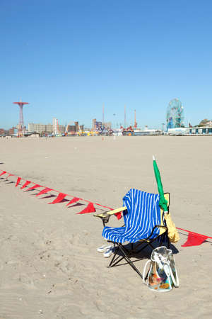 sitter: empty chair with towel on sunny coney island beach waits for sitter  to return