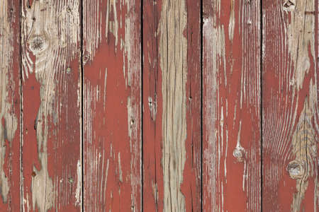 worn structure red: closeup of old brown red planks with peeling paint forms abstract pattern
