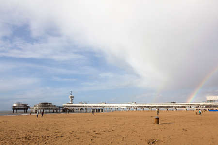 scheveningen: people on beach near scheveningen pier with cloudy sky and rainbow in afternoon sun