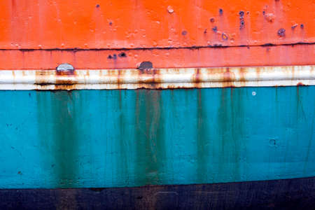 hull: rusty metal bow of old fisher boat hull in orange blue and white
