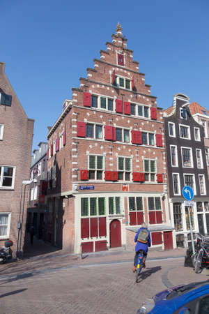 red light district: woman on bicycle passes old house in amsterdam red light district on sunny day in winter Editorial