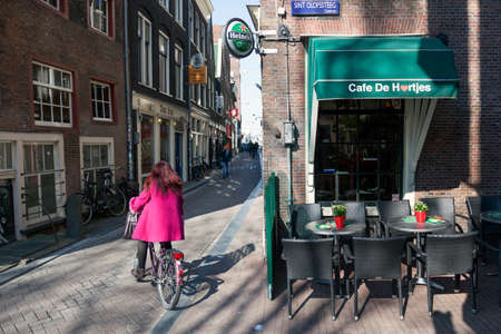 day light: girl in pink coat on bicycle in amsterdam red light district on sunny day near old bar Editorial