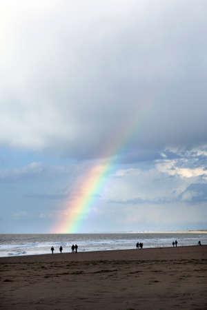 stroll: people stroll on north sea beach in holland near scheveningen with cloudy sky and rainbow