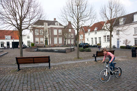 veluwe: young boy with bicycle enjoys nice spring day on vismarkt in old dutch town of harderwijk
