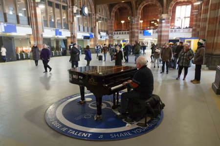 17 march: amsterdam, 17 march 2016: elderly man at grand piano for everyone to use in hall of central station amsterdam