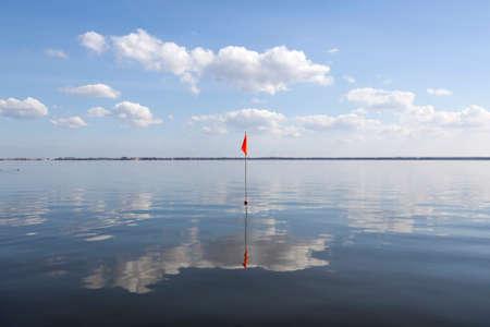flevoland: orange flag in deserted lake in the netherlands of the coast of Flevoland opposite harderwijk