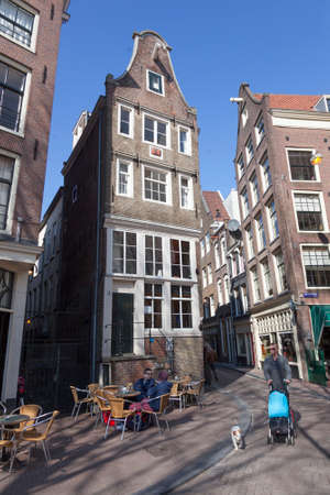 red light district: man with dog and child passes terrace in amsterdam red light district on sunny day in spring Editorial