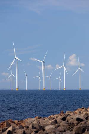 アイセル湖の水の風力タービンと青い空、オランダのフレヴォラント州の海岸をオフします。 写真素材