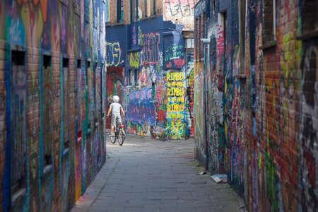 jong kind op de fiets tussen de muren vol met grafiti in de Belgische stad Gent