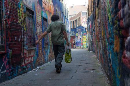 Man loopt met de boodschappen tussen de muren vol met grafiti in de Belgische stad Gent