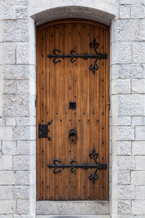 ironwork: thick ornate old door with ironwork in sandstone wall of old building in belgian town of Ghent Stock Photo