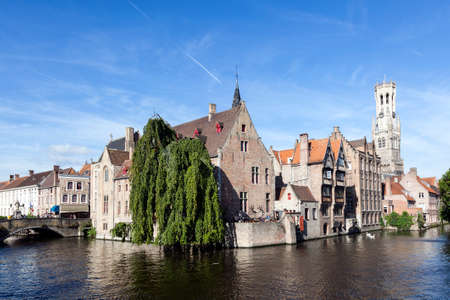 old houses along canal in centre of medieval Brugge in Belgium with blue sky in summer Editorial