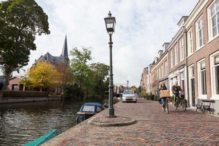 couple on bicycle passes houses along river Vecht in the dutch village of Maarssen in the netherlands