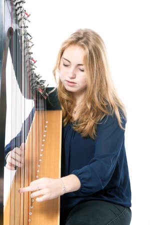 arpa: rojo rubio caucásico adolescente toca el arpa contra el fondo blanco del estudio