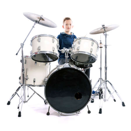 teenage boy behind drum kit in studio against white background