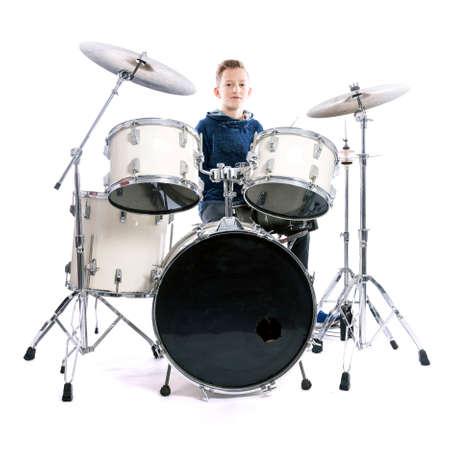 tiener achter de drum kit in studio tegen een witte achtergrond Stockfoto