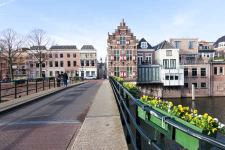 flowers on bridge over river linge and old houses in centre of old dutch town gorinchem