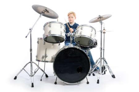 Jonge blonde jongens drums achter drum kit tegen witte achtergrond in studio Stockfoto