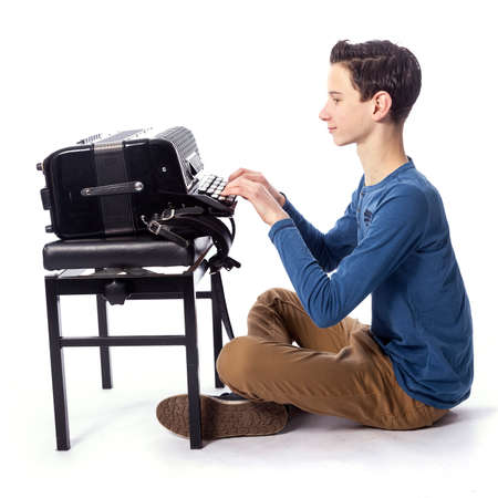 teenage caucasian boy sits with accordion on floor of studio with white background