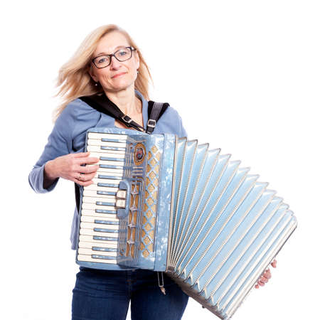 blond woman in blue with glasses plays the accordeon and smiles in studio with white background Stock Photo