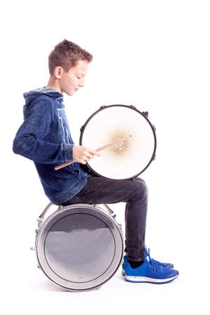 teenage boy sits with drum in studio against white background