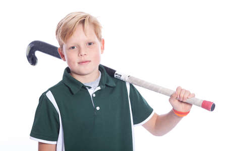 blond boy with field hockey stick in studio against white background