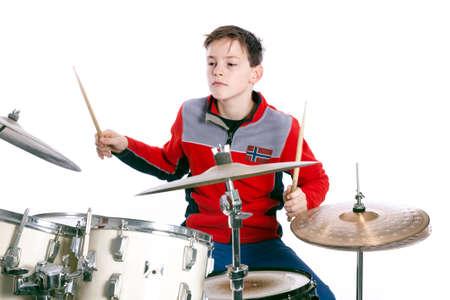 Teenage Kaukasische jongen speelt drums in studio met witte achtergrond