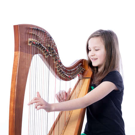 young girl in black shirt plays harp in studio against white background