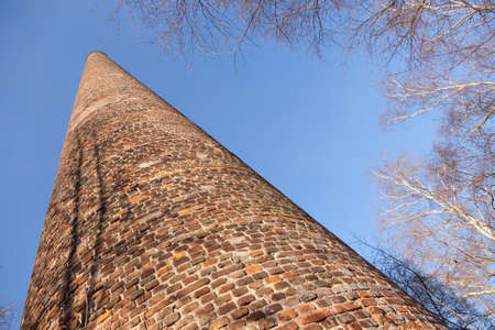 old brick factory chimney and birch trees under blue sky in the netherlands