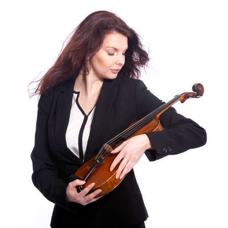 classical brunette beauty in suit holds violin in studio against white background