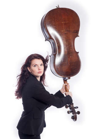 cellos: beautiful brunette woman uses cello as quirky baseball bat in studio against white background