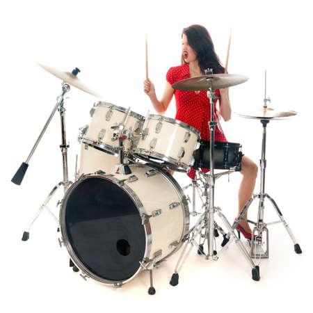 sexy brunette in rode jurk speelt drumstel in studio tegen een witte achtergrond Stockfoto