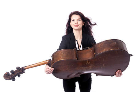beautiful brunette woman offers old brown violoncello in studio against white background