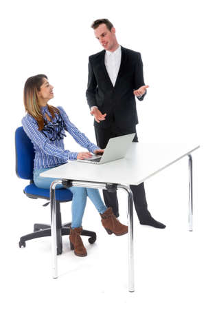 smiling secretary with laptop at table and boss seem happy with result in studio against white background and she is cheering Stock Photo