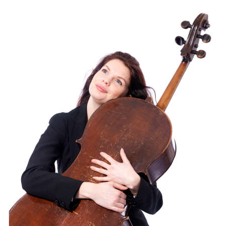 beautiful brunette woman embraces old brown violoncello in studio against white background