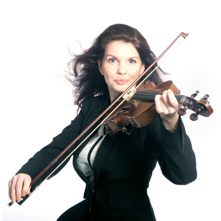 fiddles: classical brunette beauty in suit plays the violin in studio against white background