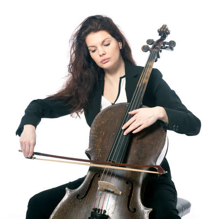 beautiful brunette woman plays old dark brown violoncello in studio against white background