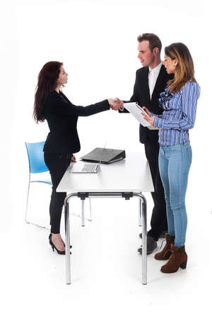 couple and business woman shake hands while standing at table in studio against white background